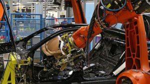 orange robotics arm working in factory