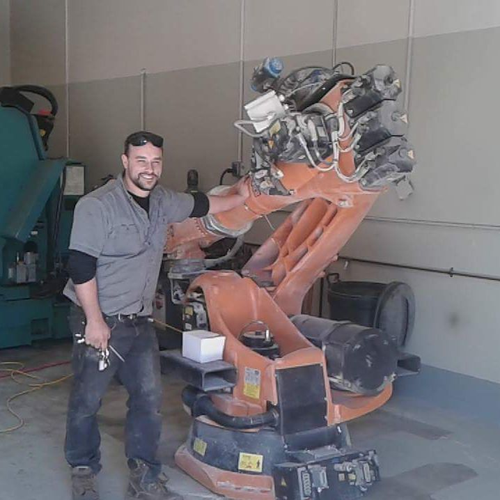 electron kmetalworks owner standing next to robotic arm